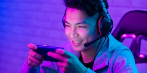 Young man wearing headphones and microphone smiling at his mobile phone
