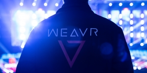 Man stood in a stadium with back to the camera wearing a black jacket with the Weavr logo on the back