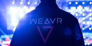 Person stood with back to camera wearing a black jacket with the Weavr logo on the back looking out across a large stadium filled with spotlights
