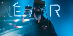 Person wearing VR headset and hand controls stood in front of a black background with the word Weavr written on it and the Weavr logo, a red triangle shape underneath