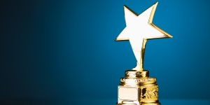 Gold star trophy pictured on a blue background