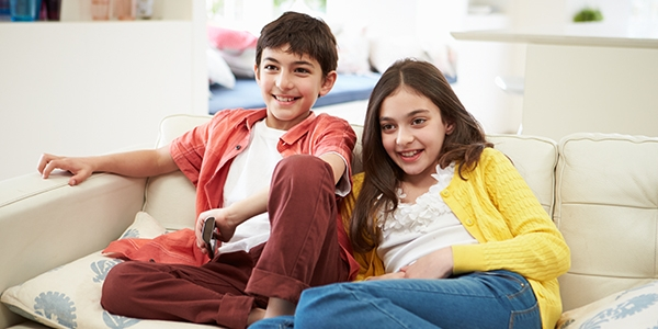 A boy and a girl sat on a sofa holding a remote control and looking excited and happy