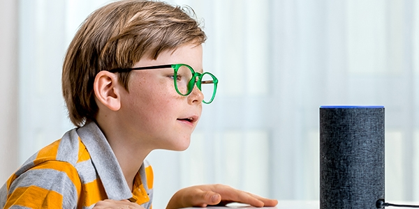 A young child with blonde hair and green glasses wearing a white and yellow striped t-shirt leaning on a table and appearing as if to say something to an Alexa home smart assistant device
