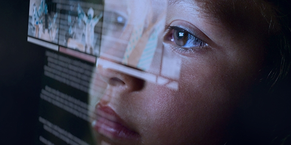 A young child with it's face very close to a screen or hologram displaying digital images and text