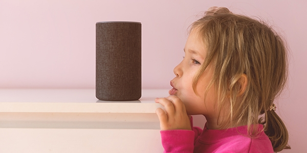 Young girl with blonde hair in a pink top whispering to a voice activated Smart device