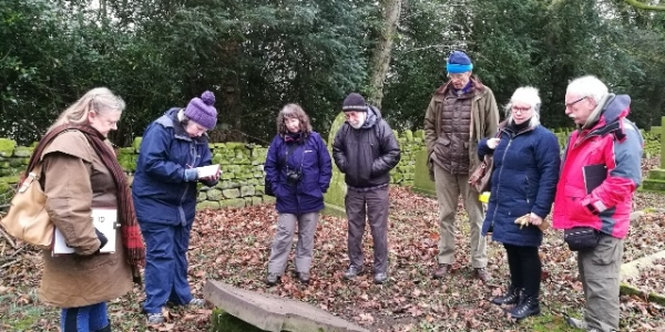 A group of people stand in a semi-circle around a gravestone in a churchyard. It is autumn and they are wearing hats and scarves. There are leaves on the ground. Some of the people are holding equipment to record gravestones including a clipboard.