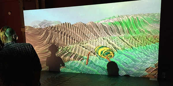 Users trying out Mutator VR Formscape projected onto a large screen