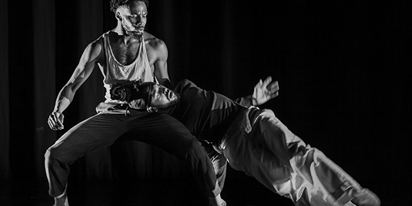 Two male dancers on a stage, one crouched in a squat position and the other with his head resting on the leg of the other dancer