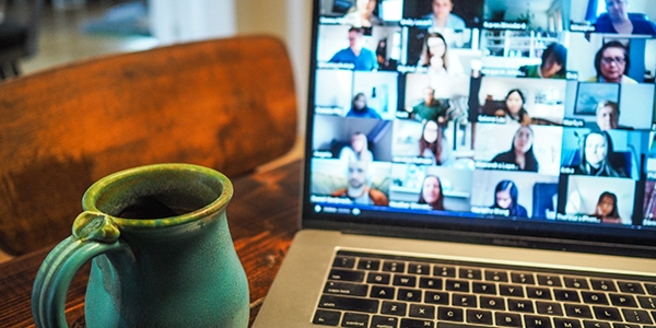 Video conference call with multiple people on a laptop screen and a turquoise mug in the foreground