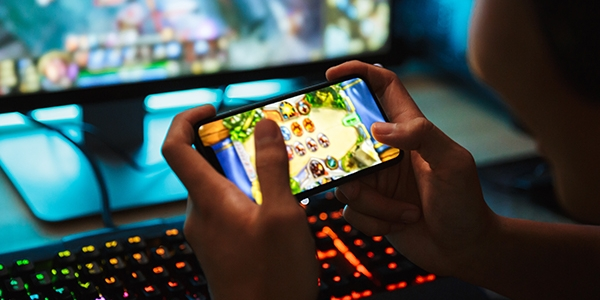 Close up of a teenager playing a mobile videogame with a larger screen in the background