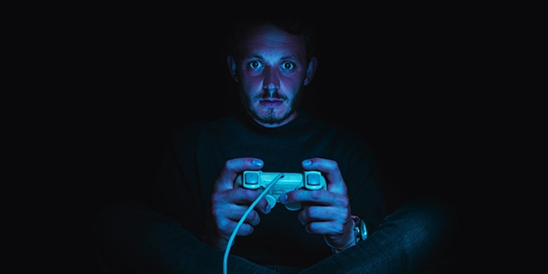 Young male in a dark room holding a games console staring avidly at the camera