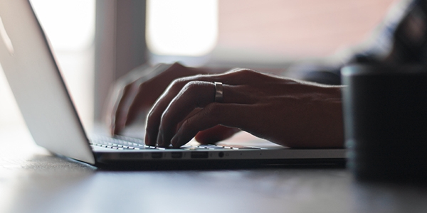 Close of female hands typing on a laptop with coffee mug to the side