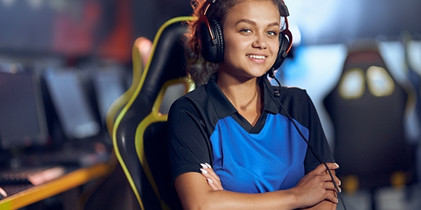 Young woman with long curly hair sat in a high backed with arms crossed wearing headphones and smiling at the camera