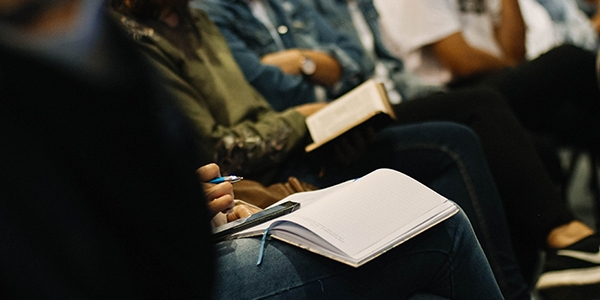 Close up of a row of people sitting on chairs holding note pads