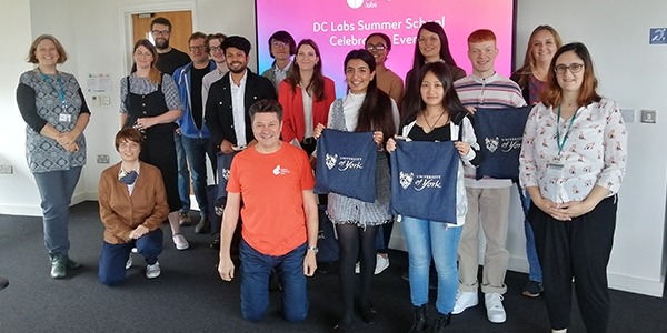 DC Labs summer school students and staff stood in front of a large video screen with a pink background displaying the text 'DC Labs Summer School celebration event'