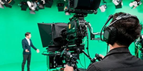 Green screen production studio with a camera operator looking into a camera facing towards a presenter stood against the green background