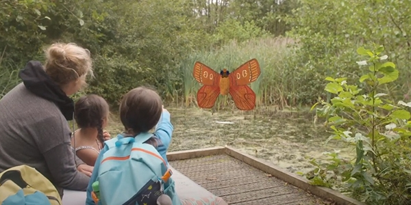 A family sitting beside a pond at Askham bog with a character from the app (Miriam Moth) super imposed in the distance