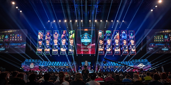 A large esports arena filled with people and multiple spotlights on a stage with esports players shown on large screens